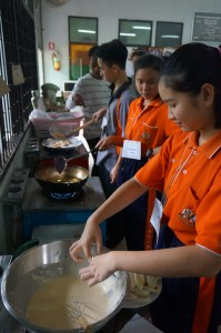 Thai students cooking pisang goreng